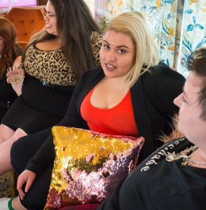 A mixed race woman with blonde hair looks at the viewer in disbelief while women sit to either side of her.